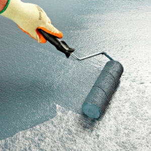 hand rolling paint on a flat roof